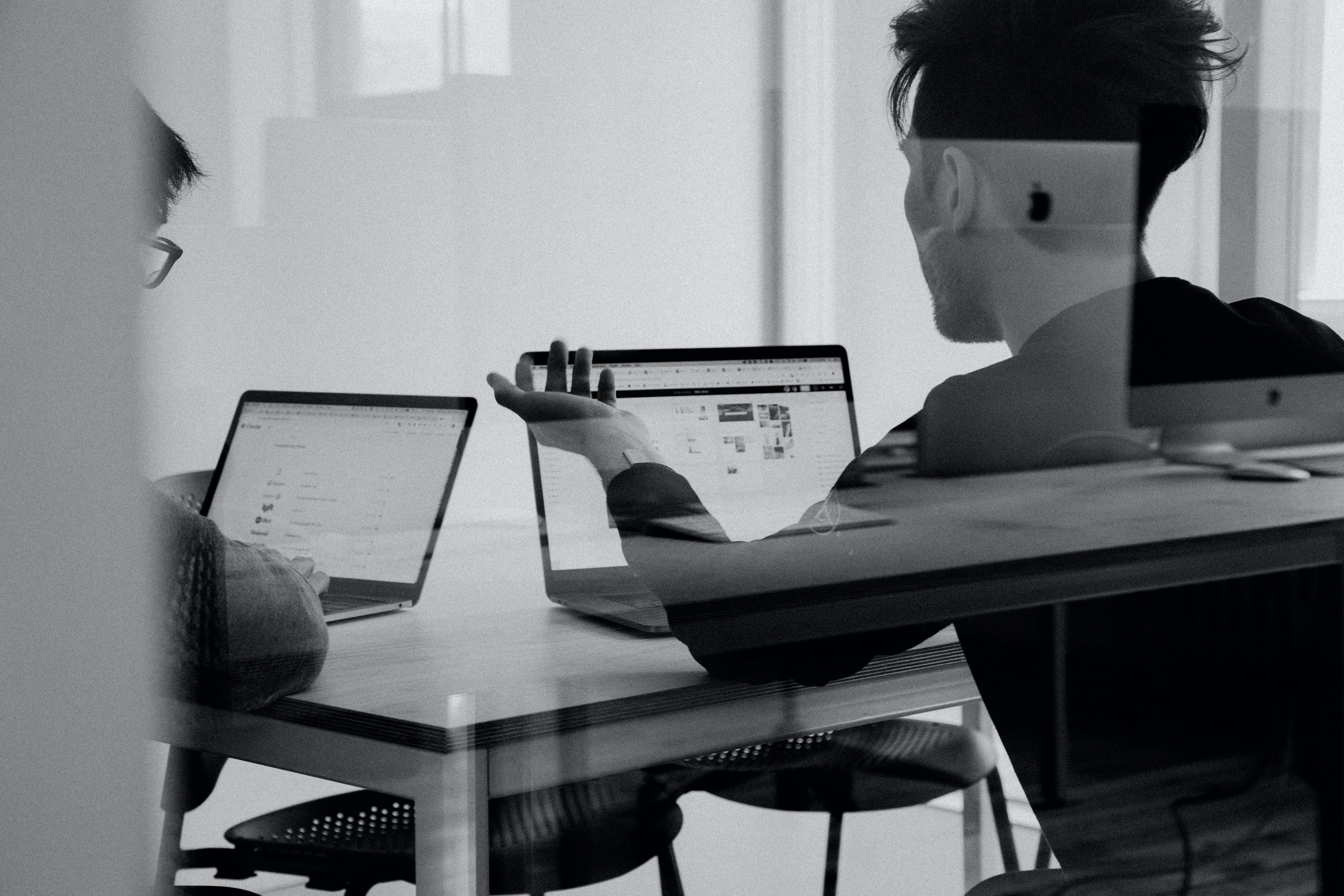 Two men conversing while working on laptops.