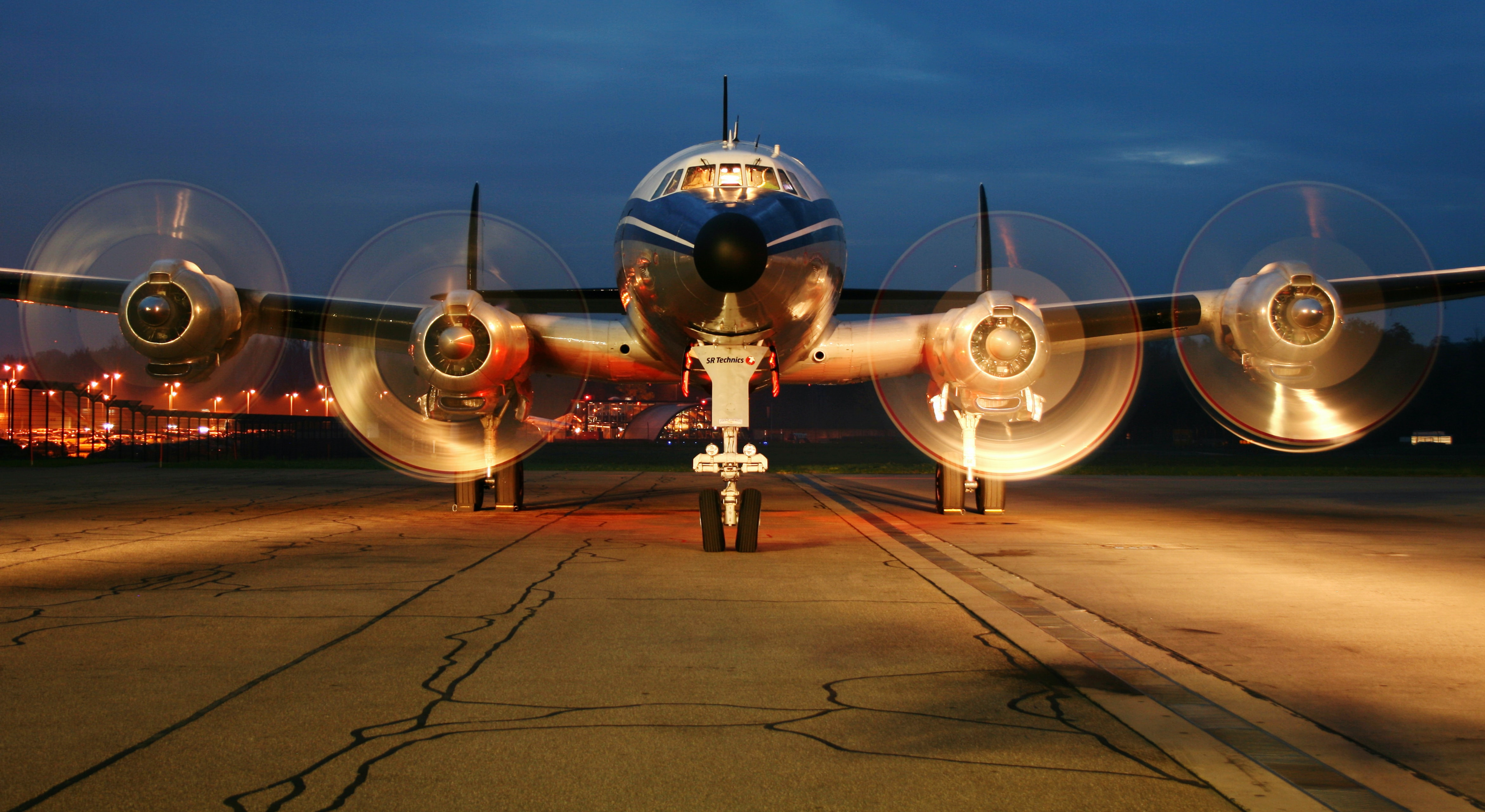 Front view of airplane with propellers spinning.